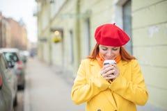 Рыжеволосая молодая женщина в желтом пальто и красном берете выпивает кофе на улице для того чтобы держать теплый стоковые изображения rf