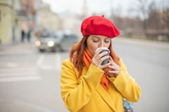 Рыжеволосая молодая женщина в желтом пальто и красном берете выпивает кофе на улице для того чтобы держать теплый стоковая фотография rf