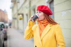 Рыжеволосая молодая женщина в желтом пальто и красном берете выпивает кофе на улице для того чтобы держать теплый стоковые изображения