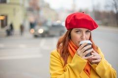 Рыжеволосая молодая женщина в желтом пальто и красном берете выпивает кофе на улице для того чтобы держать теплый стоковое изображение