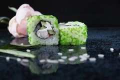 Рiece of sushi with caviar. Green land. Green caviar. Sushi on the glossy surface of the table. Sushi with tobiko caviar and shrimp royalty free stock photos