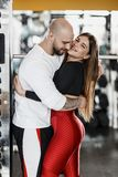 Романтичные счастливые атлетические пары Сильный человек и худенькая красивая девушка обнимают в современном спортзале рядом со с стоковые фотографии rf