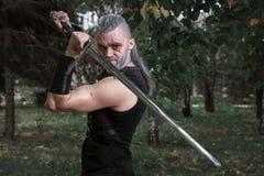 Ñ- osplay, wie ein Held Geralt von Rivia vom Spiel das Witcher gekleidet, ein fantastischer Krieger mit einer Klinge in seinen H stockfoto