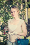 Ñ  heerful młoda kobieta trzyma ogrodniczych narzędzia w ogródzie fotografia royalty free