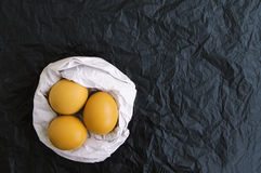 Тhree yellow Easter eggs in a nest from white paper Royalty Free Stock Photography