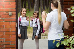 Ьother seeing her two daughters off to school Stock Photo