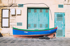Тraditional fisherman boat on the pavement in front of the boat. Colorful Malta, traditional fisherman boat on the pavement in front of the boat dock Royalty Free Stock Image