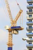 Żółci żurawie w budowie z niebieskim niebem i chmurą zdjęcia royalty free