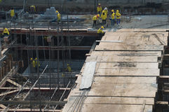 Żółci apartamentów pracownicy pracuje z betonowymi żelazami zdjęcie stock