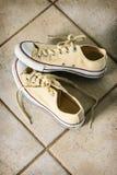 Żółci brezentowi działający buty na dachówkowej podłoga Zdjęcia Royalty Free