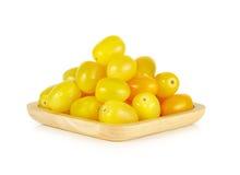 Żółci czereśniowi pomidory w drewnianym talerzu na białym tle Fotografia Stock