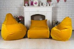 Żółci elastyczni i nastawczy siedzeń beanbags w wnętrzu Fotografia Stock