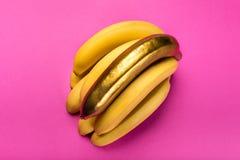 Żółci i złoci banany odizolowywający na menchiach, dojrzali banany Obrazy Stock