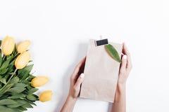 Żółci tulipany i kobiet ręki z prezentów pudełkami na białym backg Obraz Royalty Free