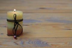 Żółta świeczka na drewnianej podłoga Zdjęcie Stock