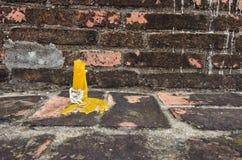 Żółta świeczka przed brown ściana z cegieł Zdjęcia Stock