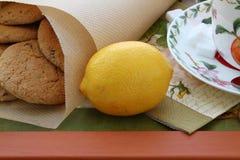 Żółta cytryna dla herbaty pić i oatmeal ciastka na tacy Zdjęcia Royalty Free