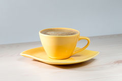Żółta filiżanka kawy na stole fotografia royalty free