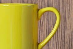 Żółta filiżanka na drewnianym brown tle Zdjęcie Stock