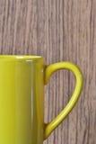Żółta filiżanka na drewnianym brown tle Fotografia Stock