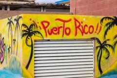 Żółta i błękitna uliczna sztuka przedstawia czarnych drzewka palmowe z słowa Puerto Rico kiścią malował na kwadratowym budynku Fotografia Royalty Free