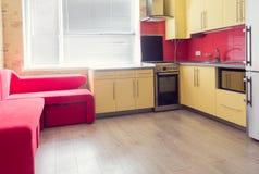 Żółta kuchnia z spiżarniami, okno, laminatem i czerwieni miękkiej części leżanką, fotografia royalty free