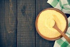 Żółta kukurydzana mąka w ceramicznym pucharze na nieociosanym drewnianym stole W obraz stock