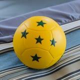 Żółta piłka z zieleni pięć gwiazdą na łóżku Obraz Stock