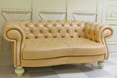 Żółta rocznik kanapa na biel ścianie Fotografia Royalty Free