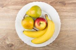 Żółte bonkrety, czerwony jabłko i banany w talerzu na stole, Zdjęcia Royalty Free