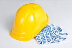 Żółte budowniczy pracy i hełma rękawiczki nad bielem Zdjęcia Stock