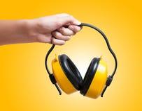 Żółte ochronne uszate mufki w ręce Fotografia Stock