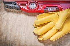 Żółte rękawiczki i czerwona budowa równi na drewnie wsiadają Obraz Stock