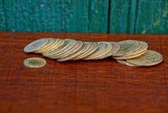 Żółte stare monety na czerwień stole Obraz Stock