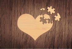Żółty łamigłówki serce na drewnianym tle Obraz Royalty Free