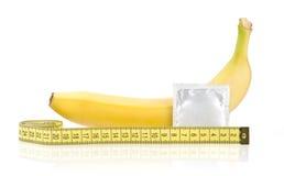 Żółty banan z kondomem i Pomiarową taśmą Fotografia Royalty Free
