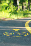 Żółty bicyklu znak na roweru pasie ruchu w parku Zdjęcie Stock