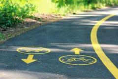 Żółty bicyklu znak na roweru pasie ruchu w parku Obraz Royalty Free