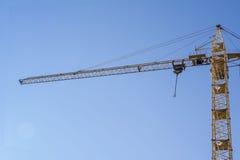 Żółty budowa żuraw na tle niebieskie niebo Fotografia Stock