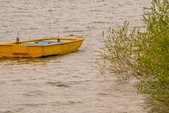 Żółty drewniany łódkowaty zagubiony w jeziorze Zdjęcie Stock
