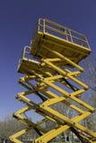 Żółty estradowy dźwignięcie na niebieskim niebie Fotografia Royalty Free