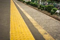 Żółty guma znak z powstaje kropki kierować niewidomych ludzi przy Depok staci fotografią brać w Depok Indonezja Obrazy Stock