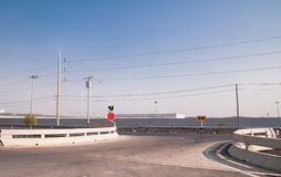 Żółty i czerwony ruchu drogowego znak na rozdrożu z mostem blisko obok Obraz Royalty Free