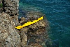 Żółty kajak na skalistym brzeg Obrazy Royalty Free