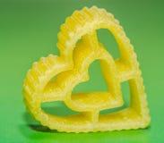 Żółty kierowy kształta makaron, zielony tło, zakończenie up Obrazy Stock