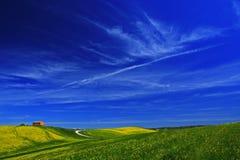 Żółty kwiatu pole z domem i jasnym zmrokiem - niebieskie niebo z białymi chmurami, Tuscany, Włochy Zdjęcia Royalty Free