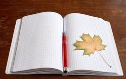 Żółty liść i pióro na copybook Obraz Royalty Free