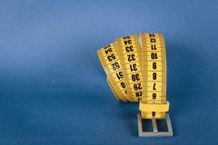Żółty metru paska odchudzanie na błękicie Fotografia Stock