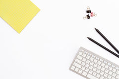 Żółty Notepad, komputerowa klawiatura, dwa czarny ołówek i klamerki dla papieru na białym tle, minimalny pojęcie desktop w daleko fotografia stock
