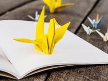 Żółty origami ptak na białym papierze Zdjęcia Royalty Free